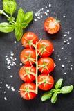 Свежие томаты вишни на черной предпосылке с специями верхняя часть соперничает Стоковые Фотографии RF