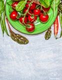 Свежие томаты вишни с свежей приправой в зеленой плите на серой деревянной предпосылке Стоковое фото RF