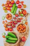 Свежие томаты вишня и огурец в прованских деревянных шарах и доске, белой предпосылке Стоковые Фотографии RF