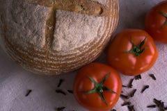 Свежие томаты, домодельный хлеб и гвоздичные деревья Стоковое Изображение RF