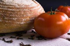Свежие томаты, домодельный хлеб и гвоздичные деревья Стоковое Изображение