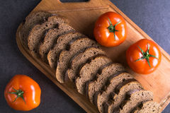 Свежие томаты при домодельный хлеб, лежа на деревянной доске Стоковая Фотография RF