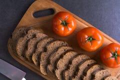 Свежие томаты при домодельный хлеб, лежа на деревянной доске Стоковые Изображения RF