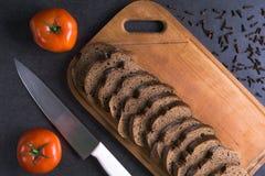Свежие томаты при домодельный хлеб, лежа на деревянной доске Стоковые Фото