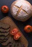 Свежие томаты при домодельный хлеб, лежа на деревянной доске Стоковое фото RF