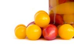 Свежие томаты рядом с опарником законсервированных томатов на белом backgro Стоковые Фото