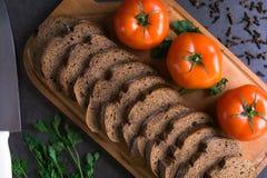 Свежие томаты с домодельным хлебом и зеленые цвета, ложь на деревянной доске Стоковые Фото