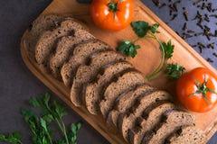 Свежие томаты с домодельным хлебом и зеленые цвета, ложь на деревянной доске Стоковая Фотография