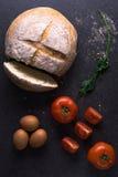 Свежие томаты с домодельным хлебом и яичками на кухонном столе Стоковое фото RF