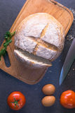 Свежие томаты с домодельным хлебом и яичками на кухонном столе Стоковые Изображения