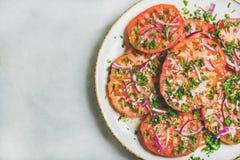 Свежие томат heirloom, петрушка и салат лука в белой плите стоковые изображения