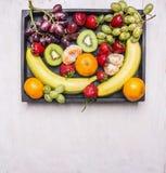 Свежие фрукты, бананы, виноградины, киви и tangerines, клубники были положены вне в винтажную деревянную клеть, взгляд сверху, ко Стоковое фото RF