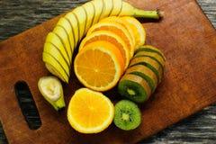 Свежие фрукты банан, киви, апельсин на деревянной предпосылке еда здоровая смешивание свежих фруктов Группа в составе цитрусовые  Стоковая Фотография RF