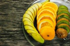 Свежие фрукты банан, киви, апельсин на деревянной предпосылке еда здоровая смешивание свежих фруктов Группа в составе цитрусовые  Стоковое Изображение RF