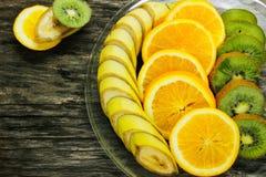 Свежие фрукты банан, киви, апельсин на деревянной предпосылке еда здоровая смешивание свежих фруктов Группа в составе цитрусовые  Стоковые Изображения RF