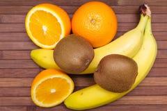 Свежие фрукты банан, киви, апельсин изолированный на деревянной предпосылке еда здоровая смешивание свежих фруктов Группа в соста Стоковые Фотографии RF