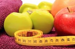 Свежие фрукты, рулетка и зеленые гантели на фиолетовом полотенце Стоковые Фото
