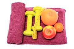 Свежие фрукты, рулетка и зеленые гантели на фиолетовом полотенце Стоковое Изображение