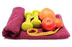 Свежие фрукты, рулетка и зеленые гантели на фиолетовом полотенце Стоковое Фото