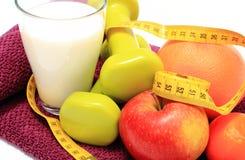 Свежие фрукты, рулетка, молоко и гантели на фиолетовом полотенце Стоковое Фото