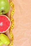 Свежие фрукты, сантиметр и гантели для фитнеса, здоровые образы жизни Стоковое Изображение
