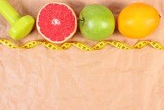 Свежие фрукты, сантиметр и гантели для фитнеса, концепции здоровых образов жизни Стоковые Изображения