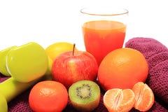 Свежие фрукты, стекло сока и гантели на фиолетовом полотенце Стоковые Изображения RF