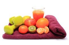 Свежие фрукты, стекло сока и гантели на фиолетовом полотенце Стоковое Изображение RF