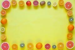 Свежие цитрусовые фрукты разделенные на желтой предпосылке Стоковые Изображения