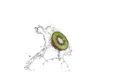 Свежие части кивиа в воде брызгают, изолированный на белой предпосылке Стоковое Фото