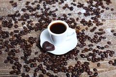 Свежие чашка кофе и кофейные зерна на таблице Стоковые Изображения