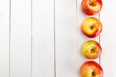 Свежие яблоки на белом деревянном столе стоковые изображения