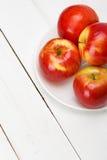 Свежие яблоки на белом деревянном столе Стоковое Изображение
