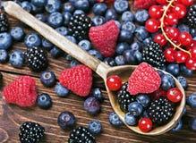 Свежие ягоды и старая деревянная ложка стоковые фотографии rf