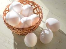 Свежие яичка в деревянной корзине на деревянной предпосылке осветили ярким солнечным светом стоковые фото