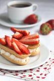 Свежие cream eclairs с взбитыми сливк и клубниками и чашкой Стоковая Фотография