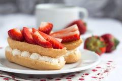 Свежие cream eclairs с взбитыми сливк и клубниками и чашкой Стоковое Изображение RF