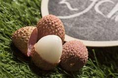 Свежие lychees на предпосылке травы Стоковая Фотография