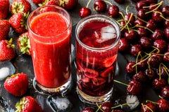 Свежие smoothie и вытрезвитель клубники мочат с вишнями в 2 стеклах на серой предпосылке Здоровые пить вытрезвителя Стоковое Изображение