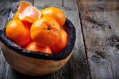 Свежие tangerines в деревянной плите на старой деревянной предпосылке Стоковое фото RF