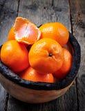 Свежие tangerines в деревянной плите на старой деревянной предпосылке Стоковое Фото