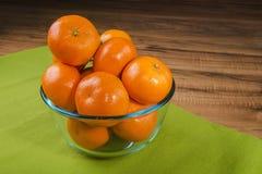 Свежие tangerines в прозрачной плите на зеленой скатерти, деревянном столе Стоковое Фото
