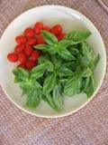 Свежий базилик и мини томаты сливы в винтажной плите на столешнице ротанга Стоковое Фото