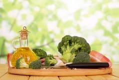 Свежий брокколи, масло бутылки, специи, нож, полотенце на абстрактном зеленом цвете Стоковое Фото