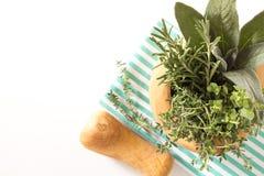 Свежий букет трав в деревянном миномете на сложенном полотенце кухни, на белой предпосылке Стоковое Изображение