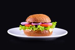 Свежий вкусный бургер изолированный на черной предпосылке Вкусный и аппетитный cheeseburger на белой плите Вегетарианский бургер стоковое изображение
