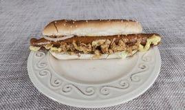 Свежий вкусный хот-дог с зажаренными луками и свежим салатом с мустардом на плите фарфора Стоковое Фото