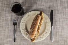 Свежий вкусный хот-дог с зажаренными луками и свежим салатом с мустардом на плите фарфора с вилкой и ножом Стоковая Фотография RF