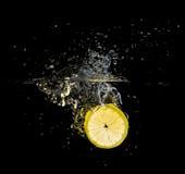 Свежий выплеск куска лимона на черноте стоковое фото rf