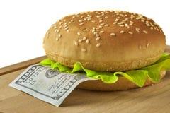 Свежий гамбургер при 100 долларовых банкнот изолированных на белизне Стоковая Фотография RF